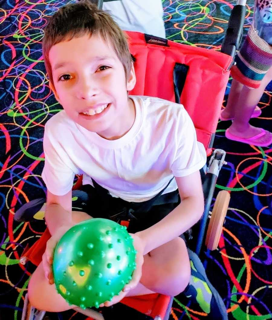 A boy with Ring14 sits in his stroller at am arcade holding a green ball