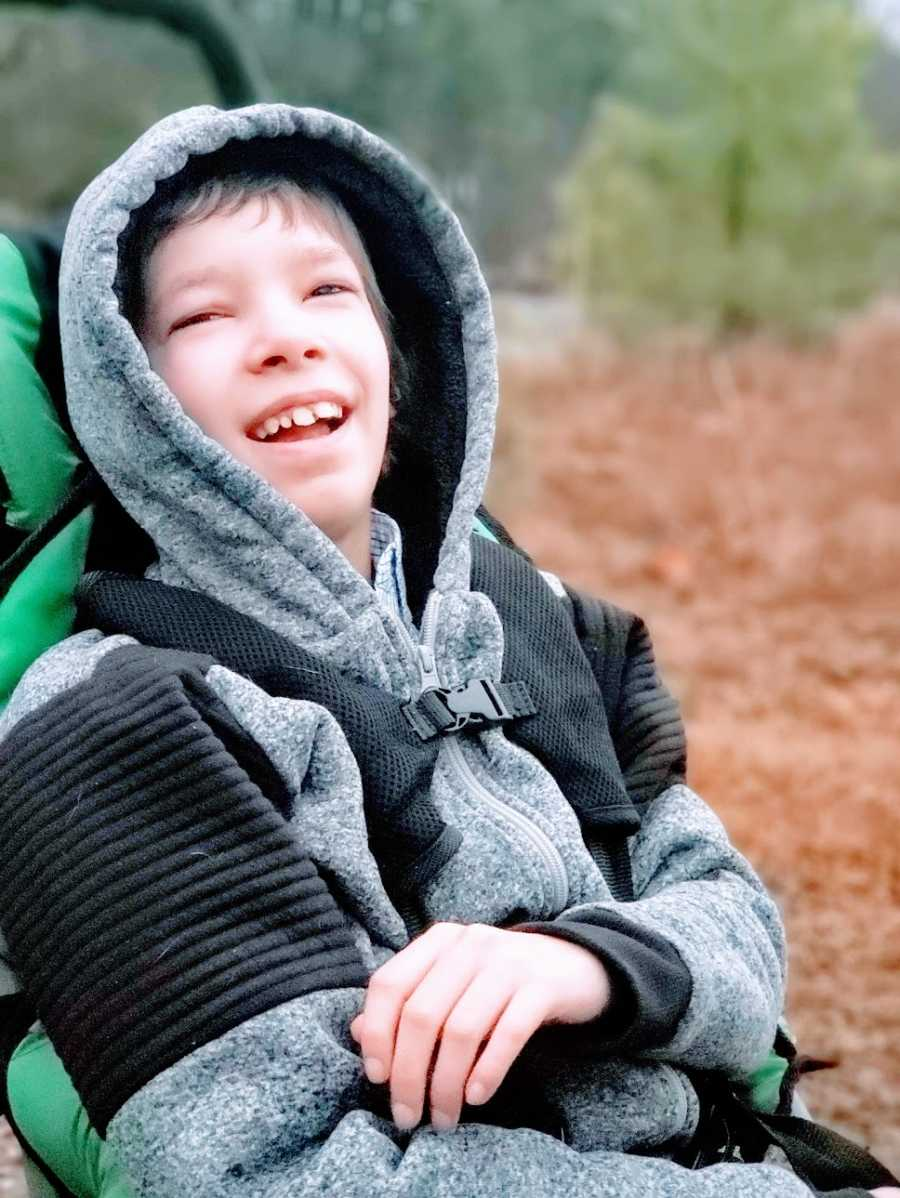 A boy with Ring14 sits in a stroller outdoors wit his hood pulled up
