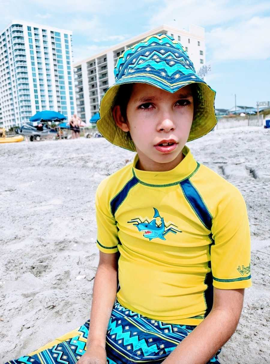 A boy with a rare chromosome condition wearing a yellow swimshirt at the beach