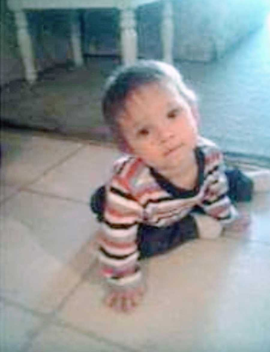 A baby boy with rare seizures sits on the floor in a striped shirt