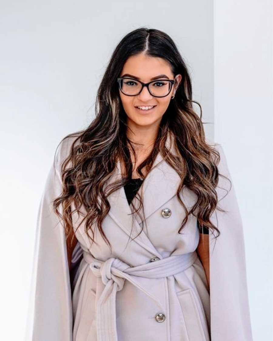 A woman with ADHD with long dark hair, glasses, and a beige overcoat