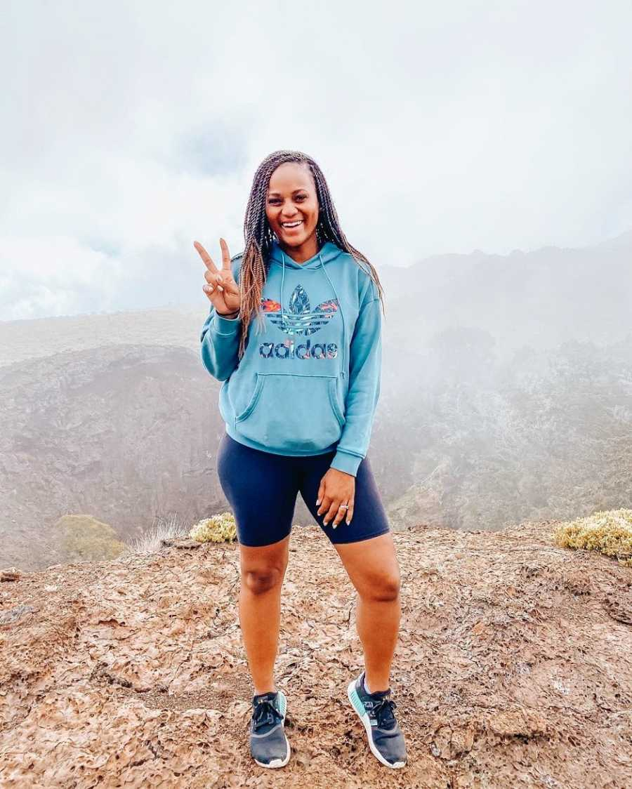 A woman in a blue hoodie making a peace sign on a volcano