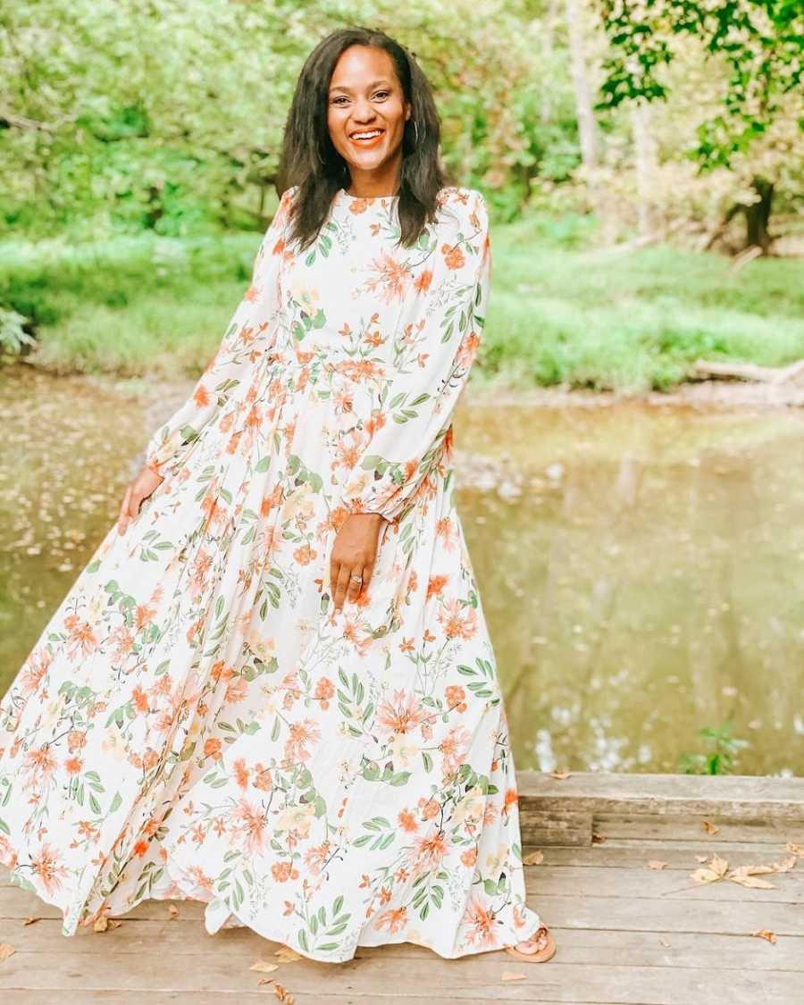 A woman wearing a floral dress stands on a bridge near a field