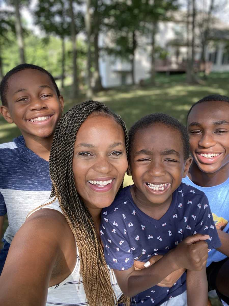 Mom standing outside with three sons smiling