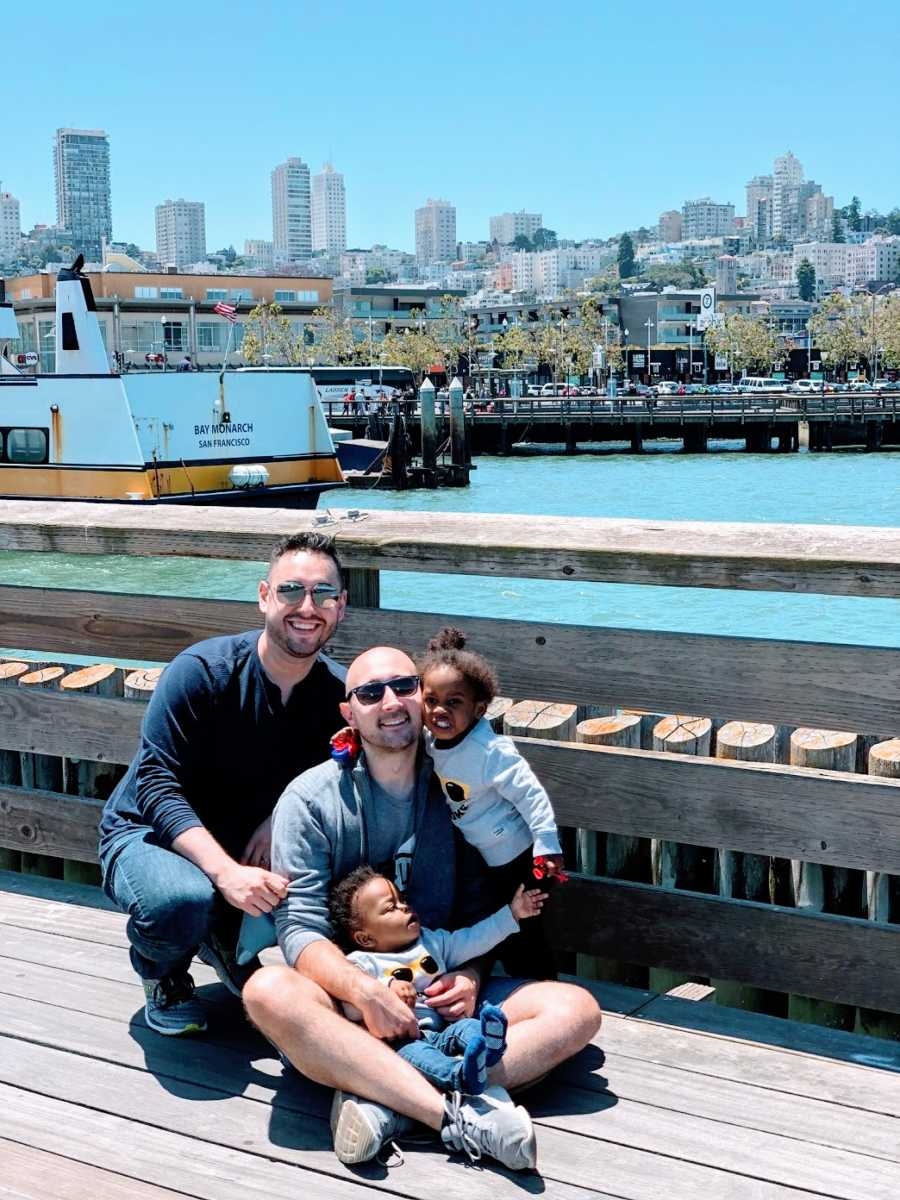 Gay fathers with their adopted toddlers at a fence by the water