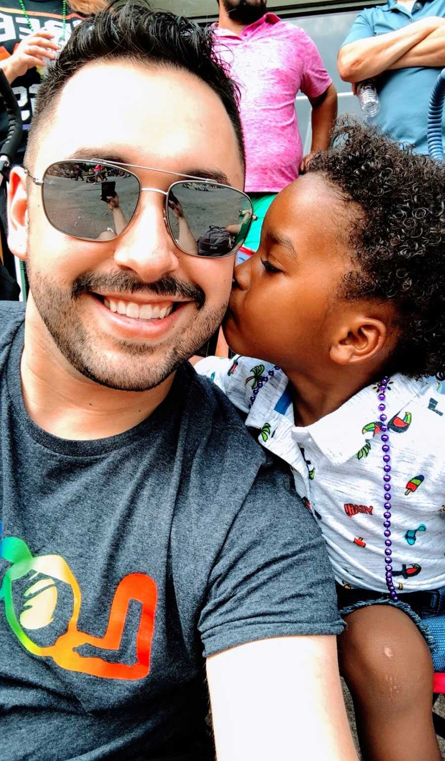 A toddler kisses his adoptive father on the cheek