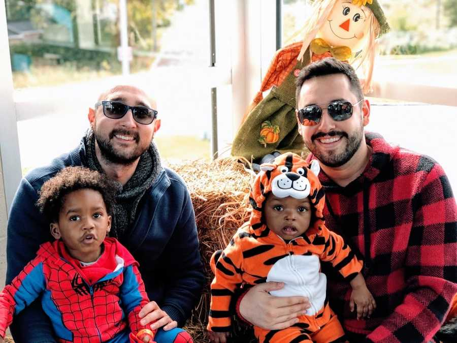 Gay fathers hold their adoptive sons who are wearing Halloween costumes
