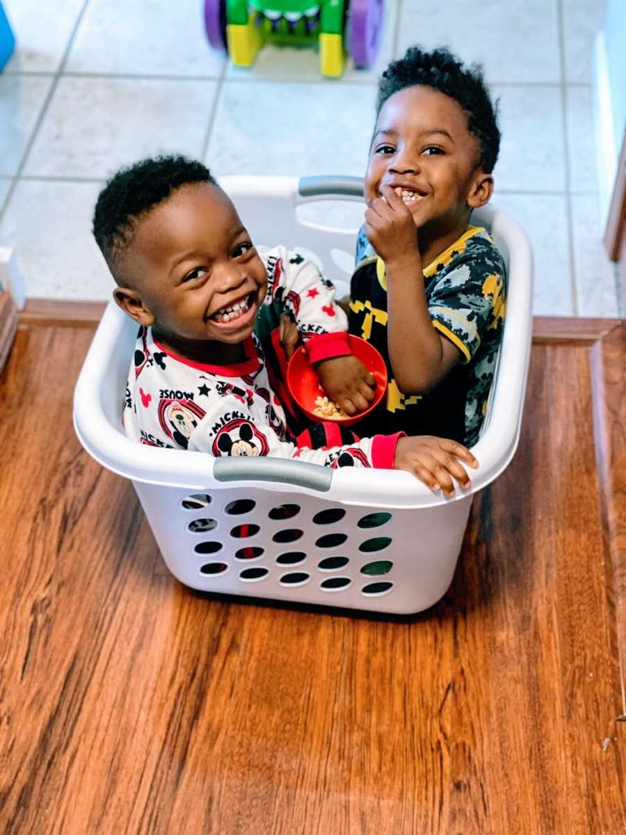 A pair of brothers sit smiling in a laundry basket