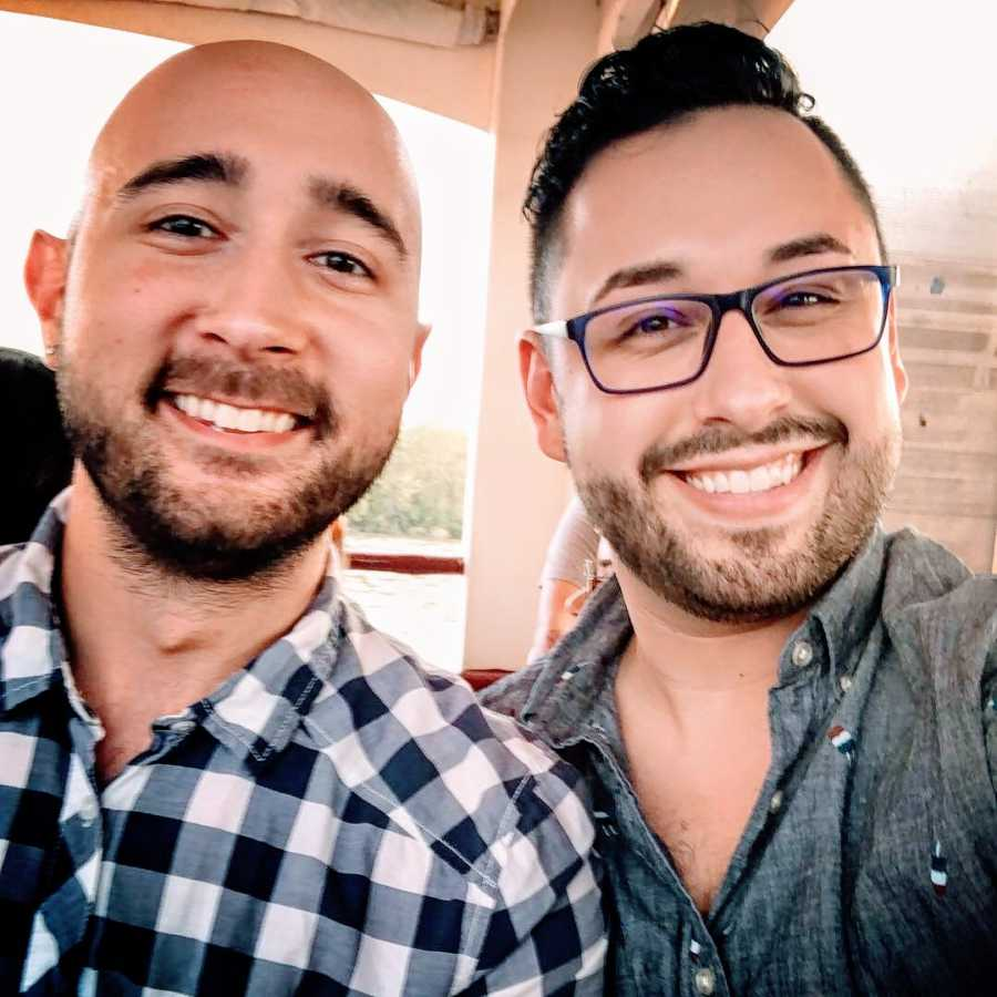 A pair of gay men, one in a checkered shirt and the other wearing glasses