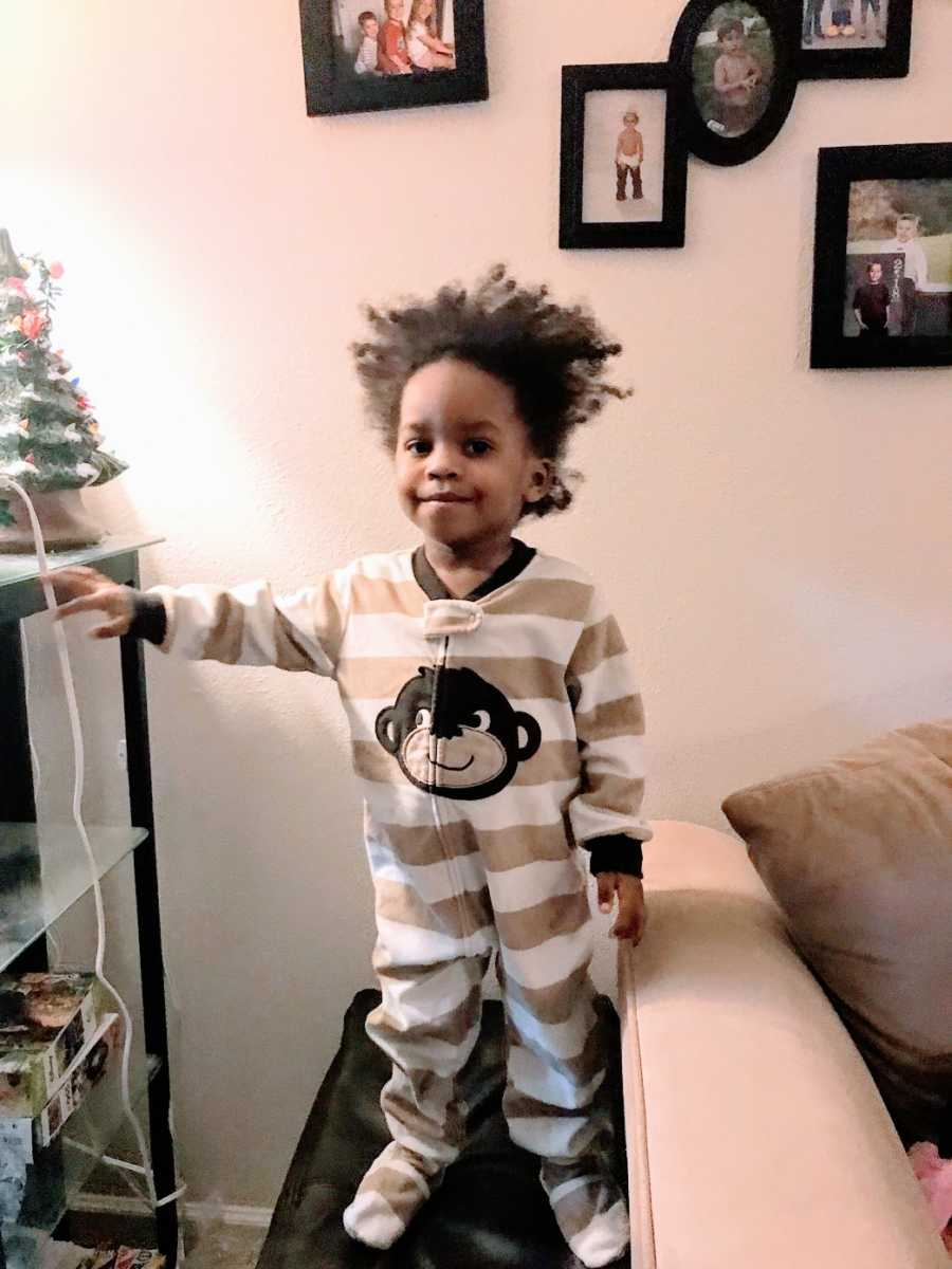 A toddler wearing pajamas stands next to Christmas decorations