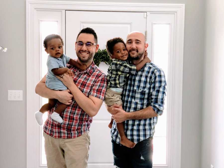 Gay fathers hold up their adoptive sons