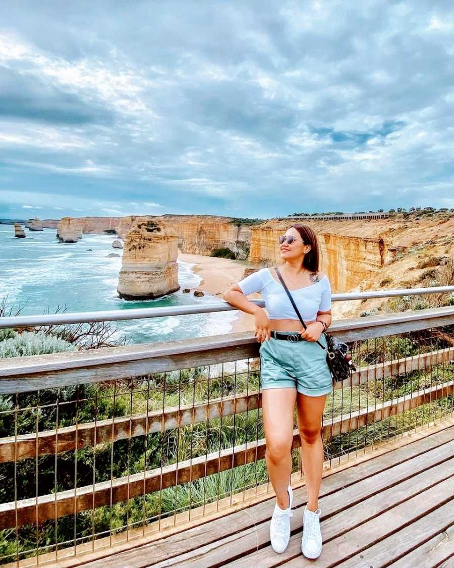 A woman stands on a bridge in front of cliffs and water