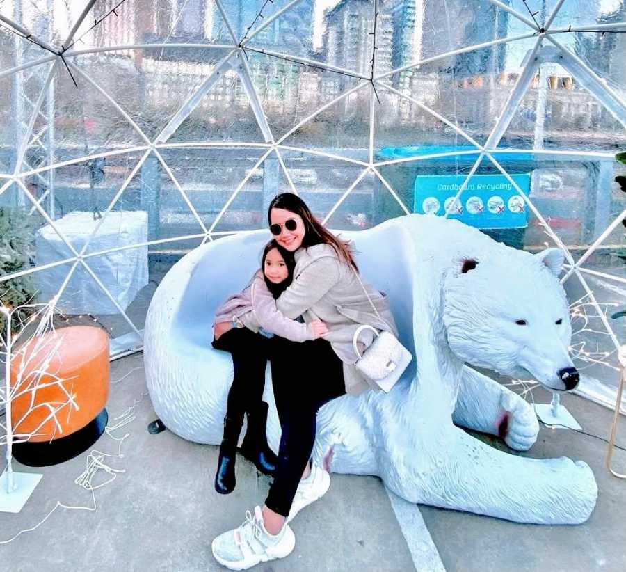 A single mother holds her daughter in a polar bear chair
