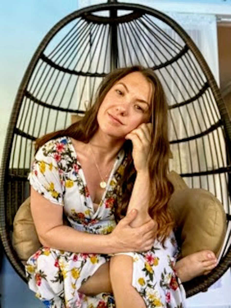 Woman sitting in basket chair with head resting on hand