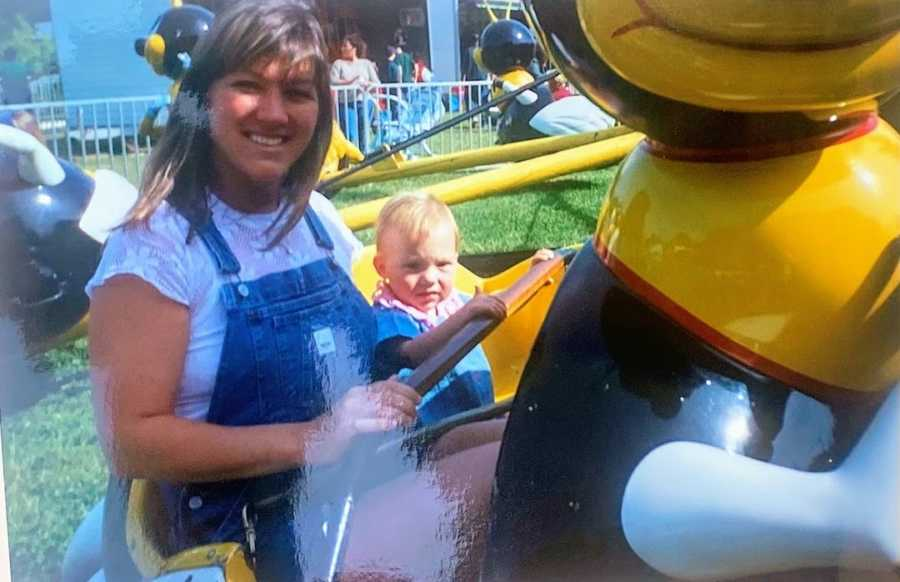 Mom riding amusement park ride with baby daughter