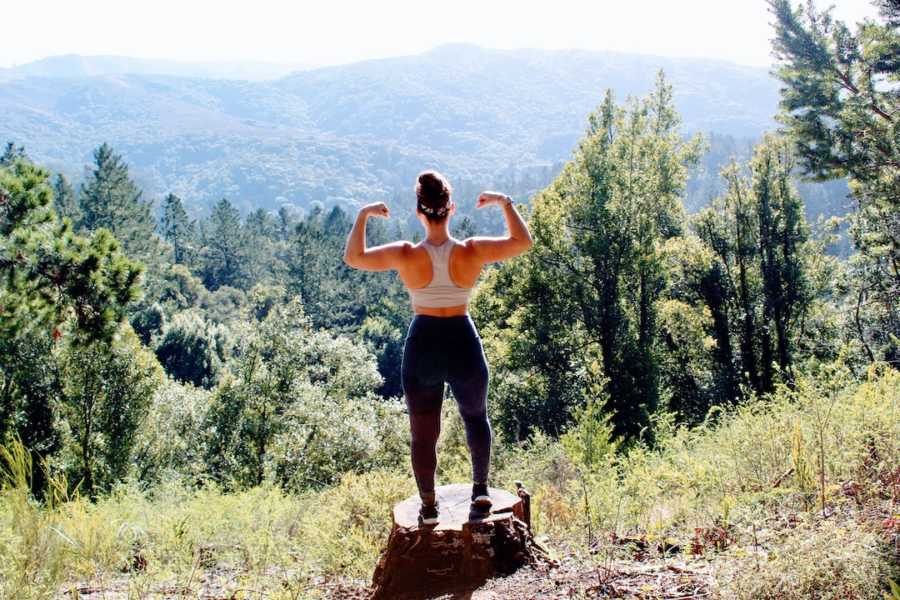 Woman flexing standing on a rock with back to camera in front of pine tree forest