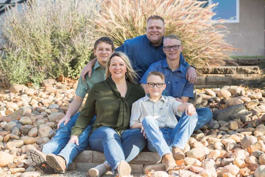 Family of five sitting outside smiling for family photo