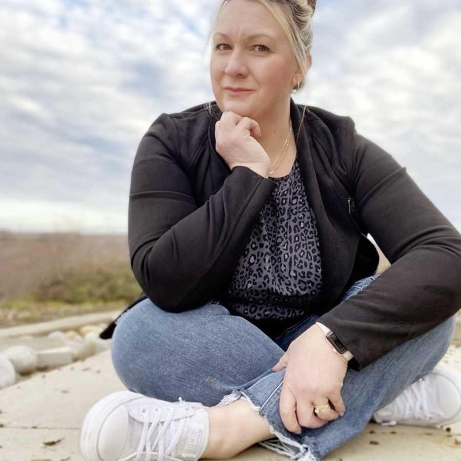 Woman sitting cross-legged outside wearing black jacket