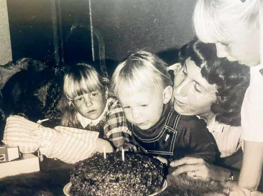 Black and white photo of mother with two daughters blowing out candles on a birthday cake