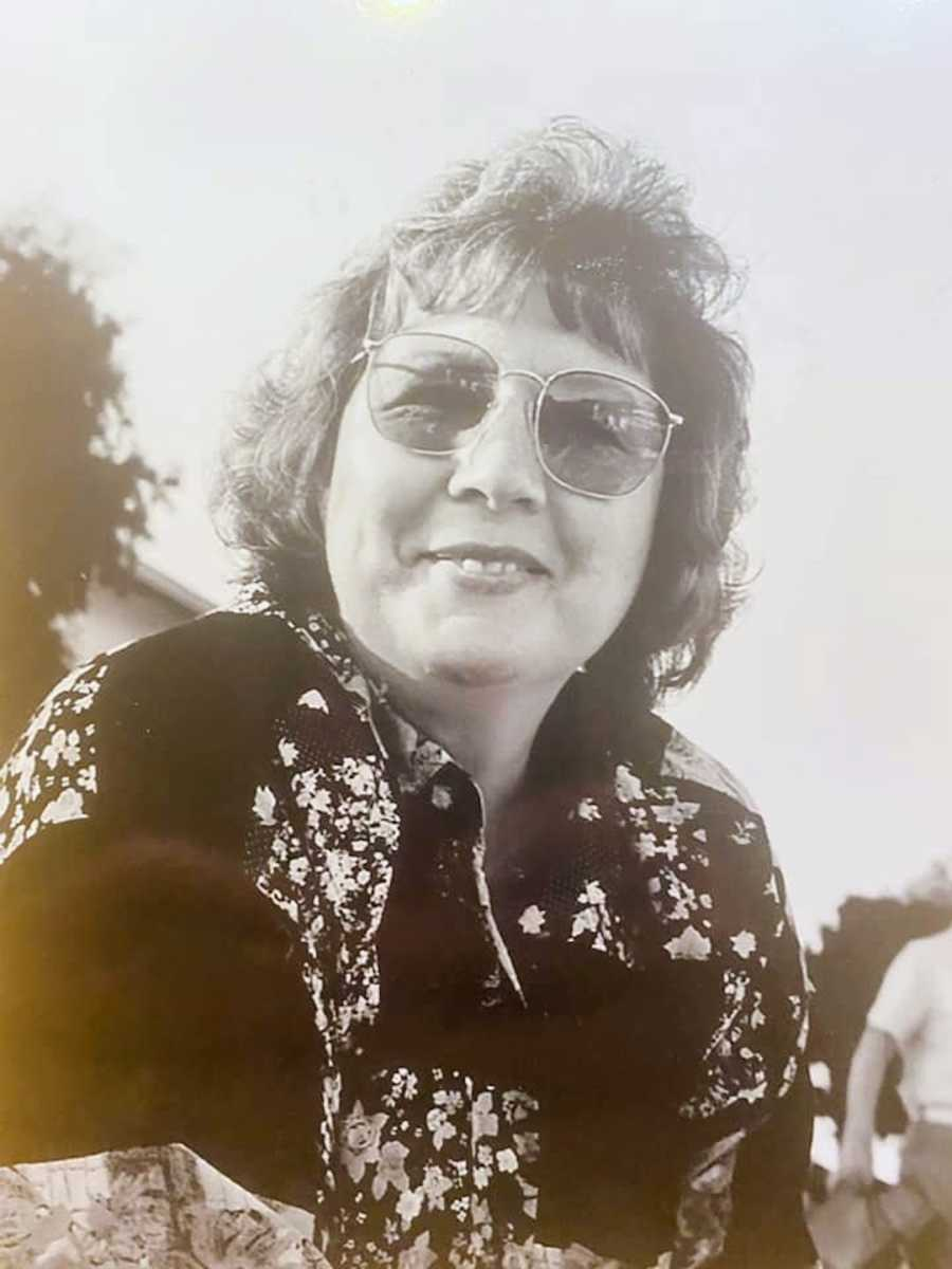 Black and white photo of woman sitting outside wearing sunglasses