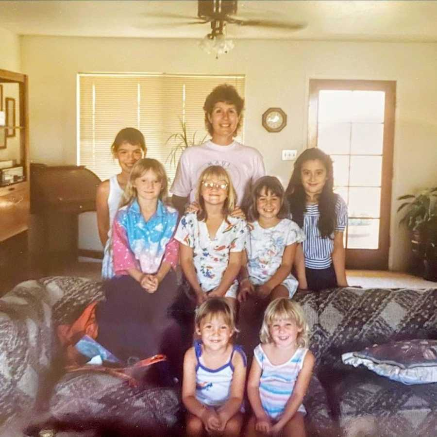 Woman standing with young family members in a living room