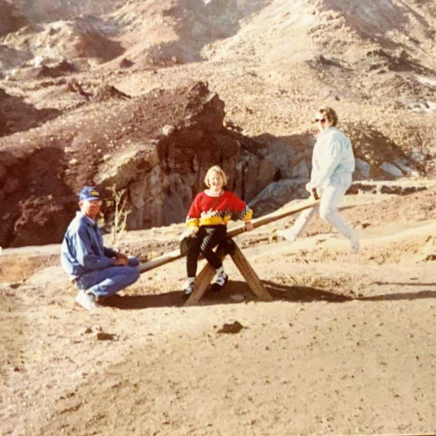 Mother and father sitting on teeter totter in desert with daughter in the middle