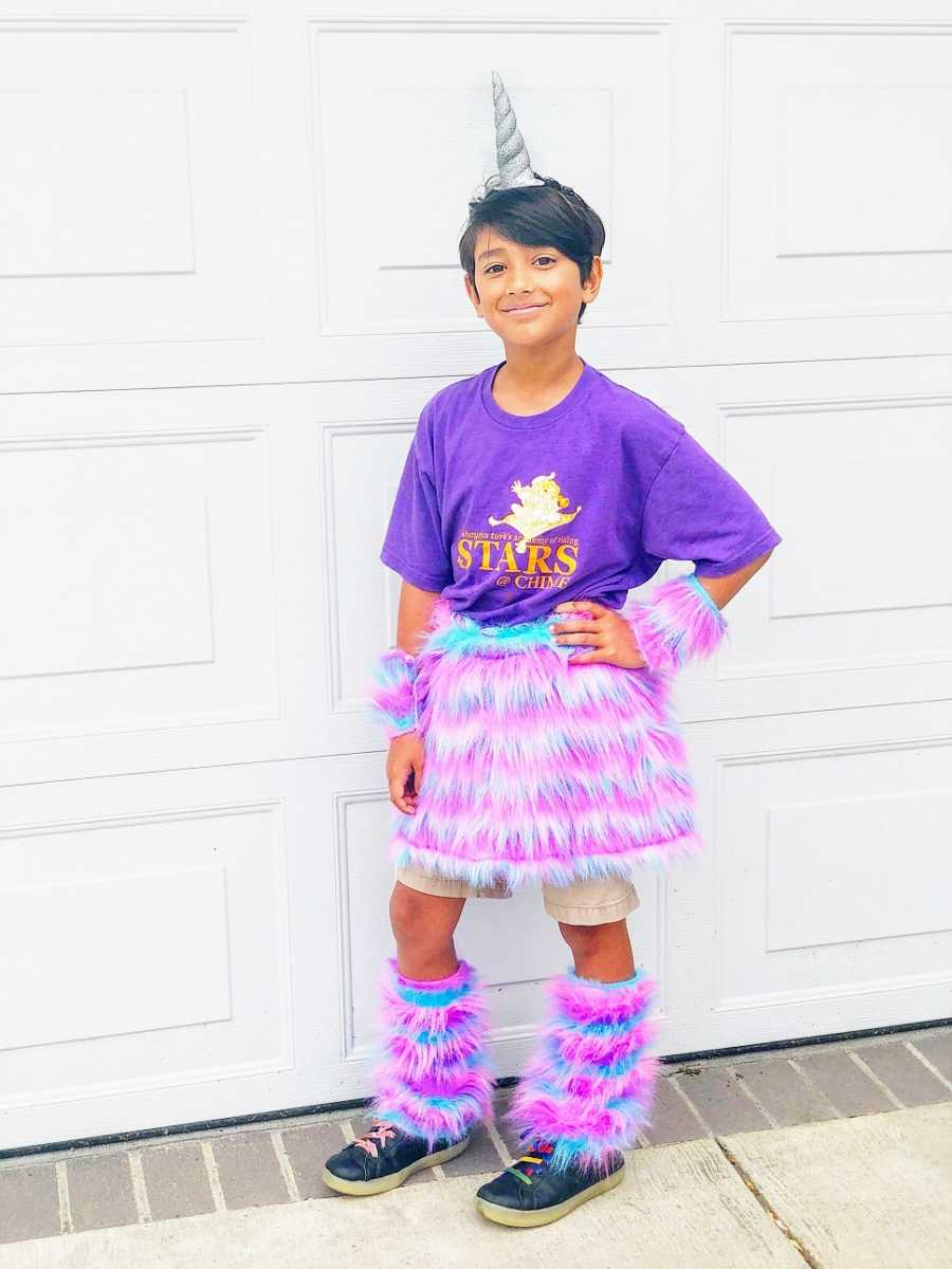 A boy wears a purple shirt and a fuzzy pink skirt