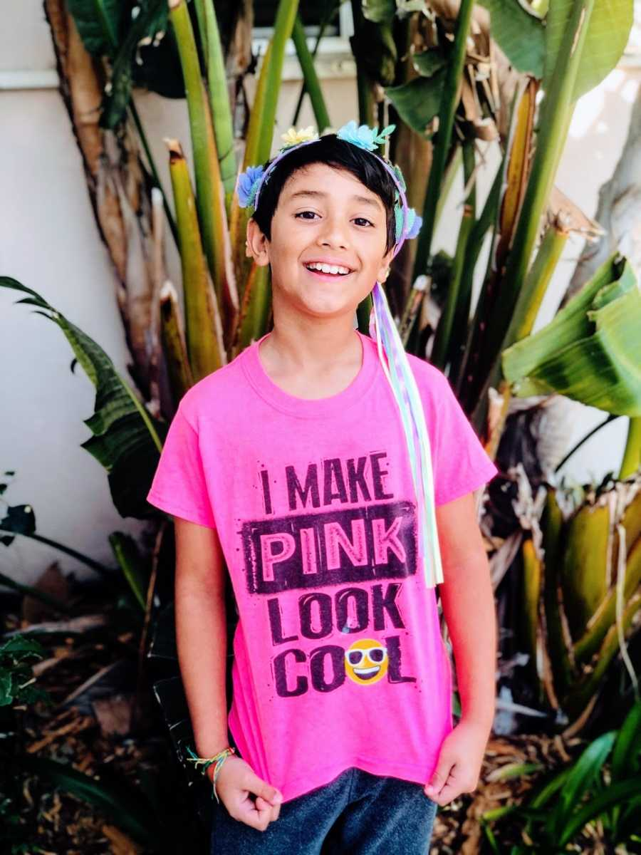 A boy wears a pink shirt and a flowery headband