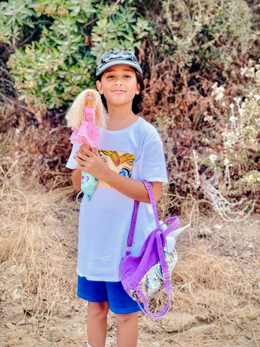A boy with a sparkly backpack holds up a doll