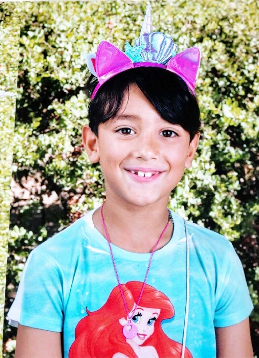 A boy wears a Little Mermaid shirt for his school picture
