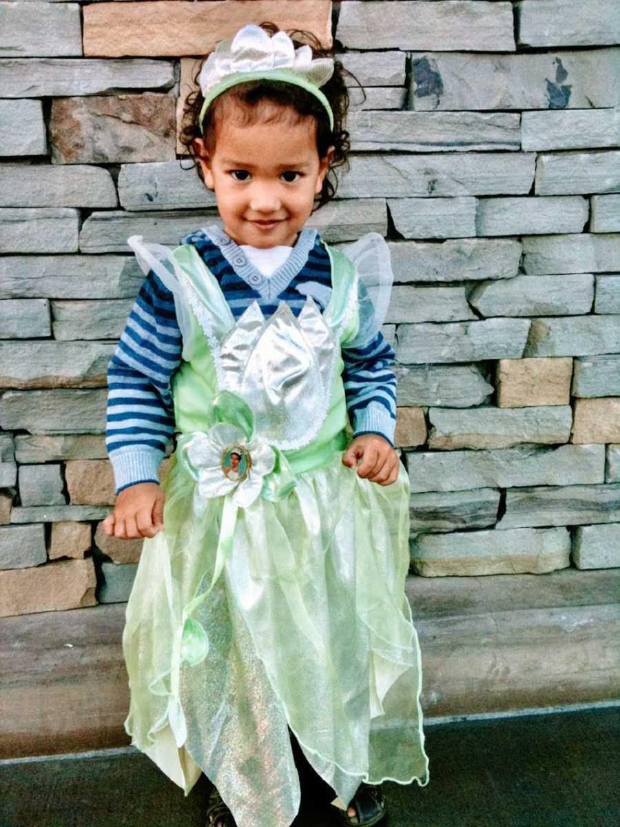 A little boy wearing a green princess dress and tiara