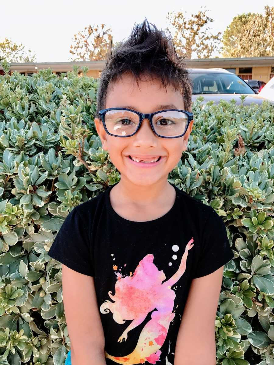 A boy wearing glasses and a pink mermaid shirt