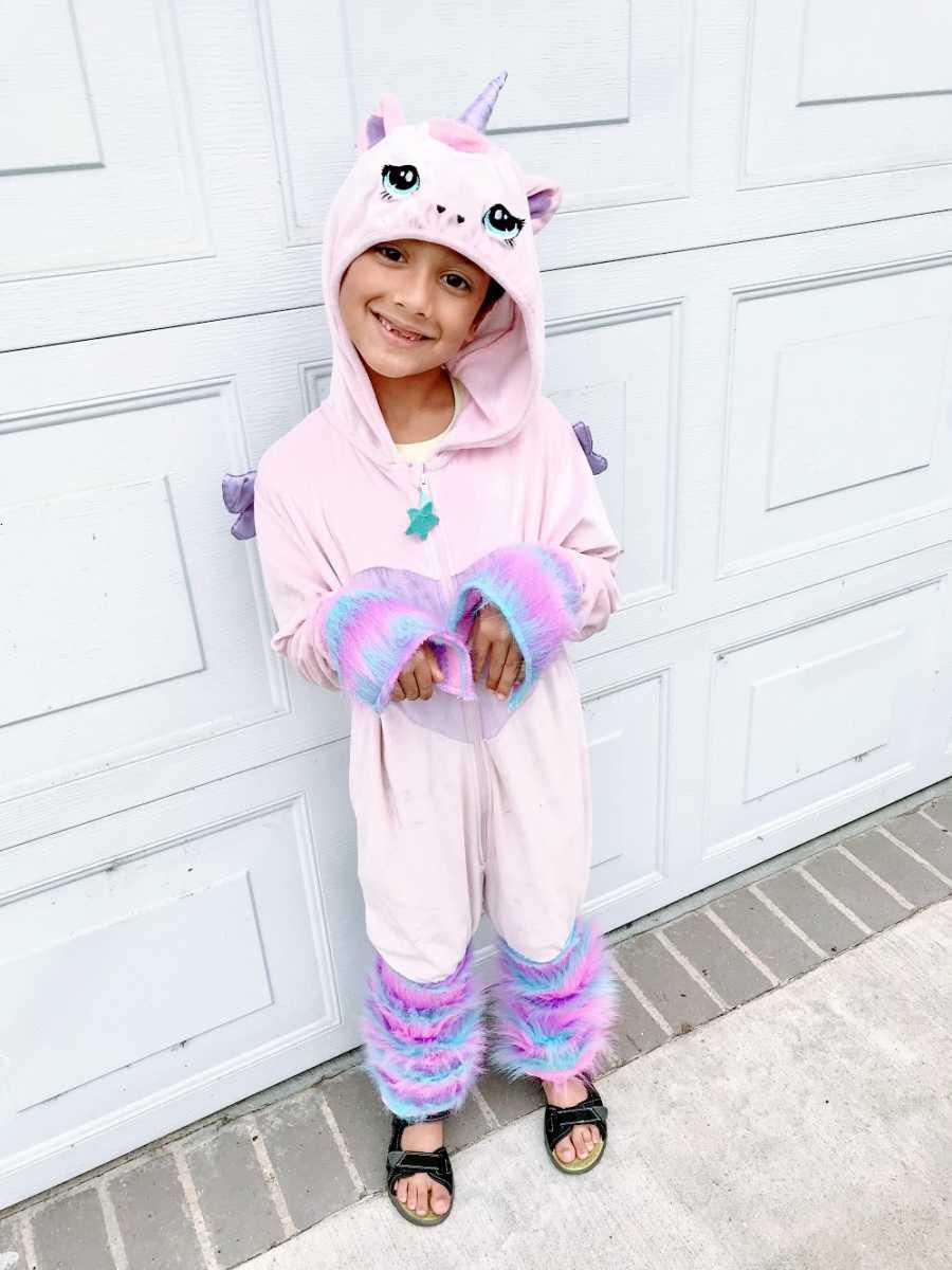 A little boy wears a pink unicorn costume