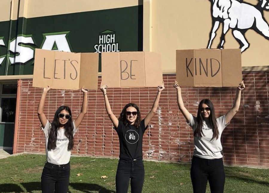 three girls with signs that spell out let's be kind