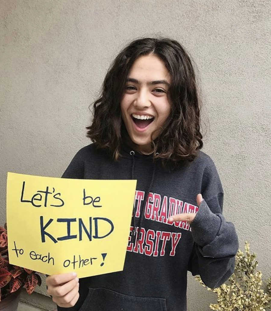 girl pointing to a sign saying let's be kind
