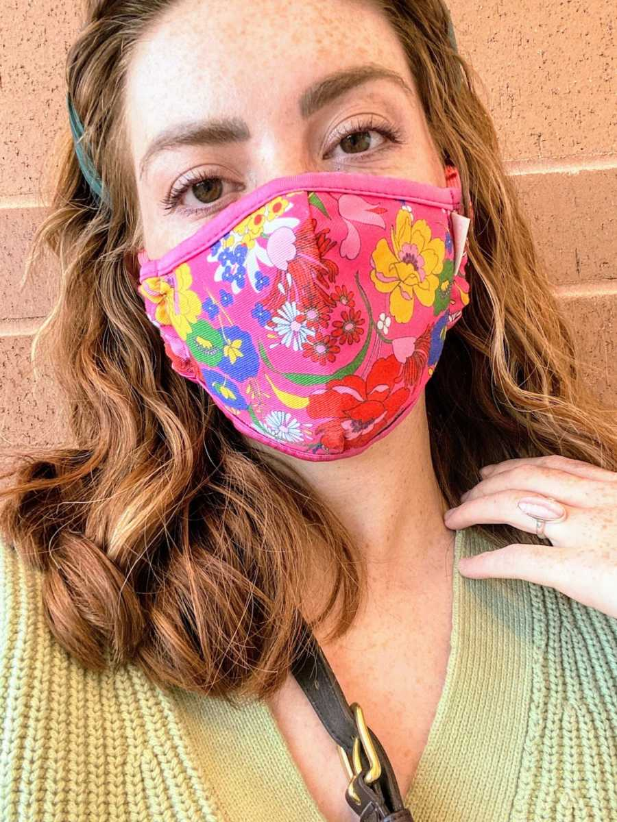 Woman wearing floral face mask in front of brick building