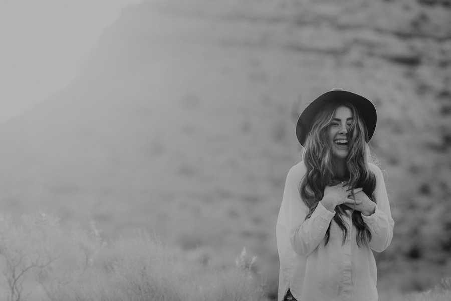 Black and white photo of woman wearing hat and laughing