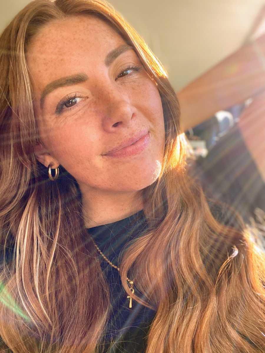 Woman taking smiling selfie in the sunlight