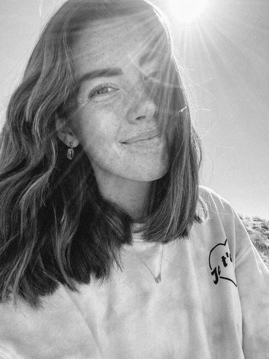 Black and white photo of woman smiling in the sunlight