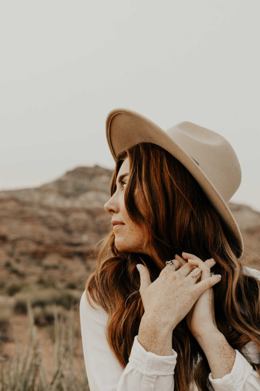 Woman wearing hat standing outside looking off into the distance
