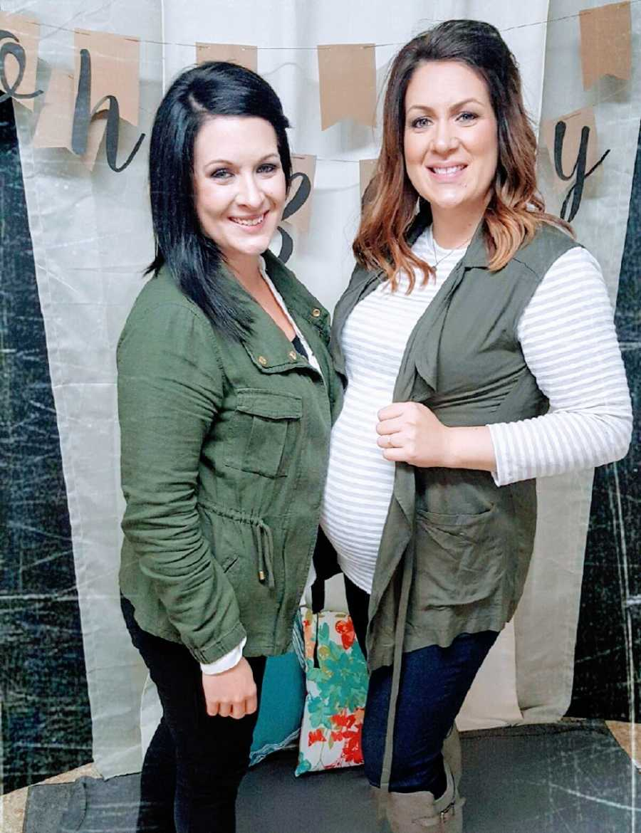 A pair of women stand together at a baby shower