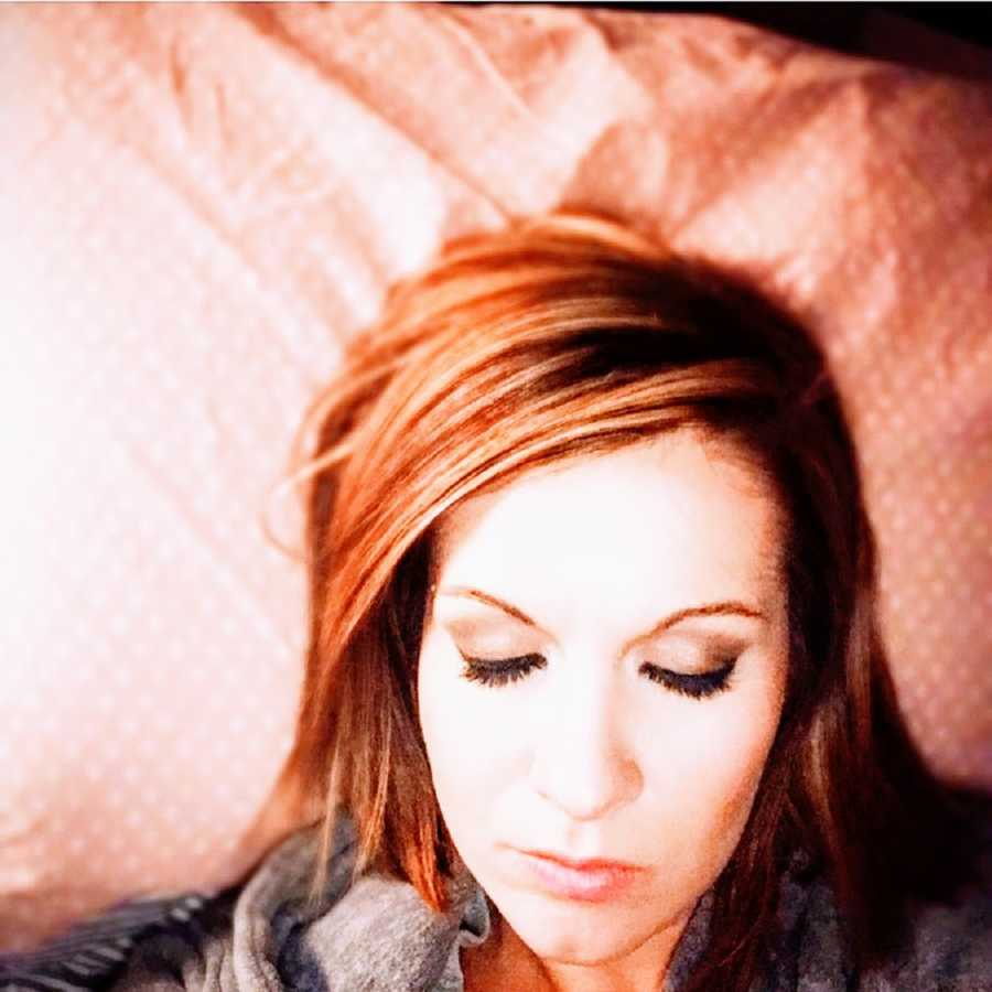 An alcoholic woman lies on her bed with her eyes closed
