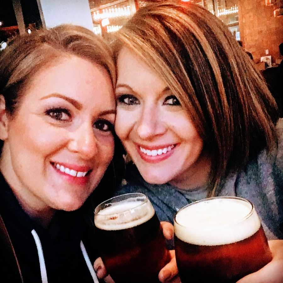 Two women drink beers together