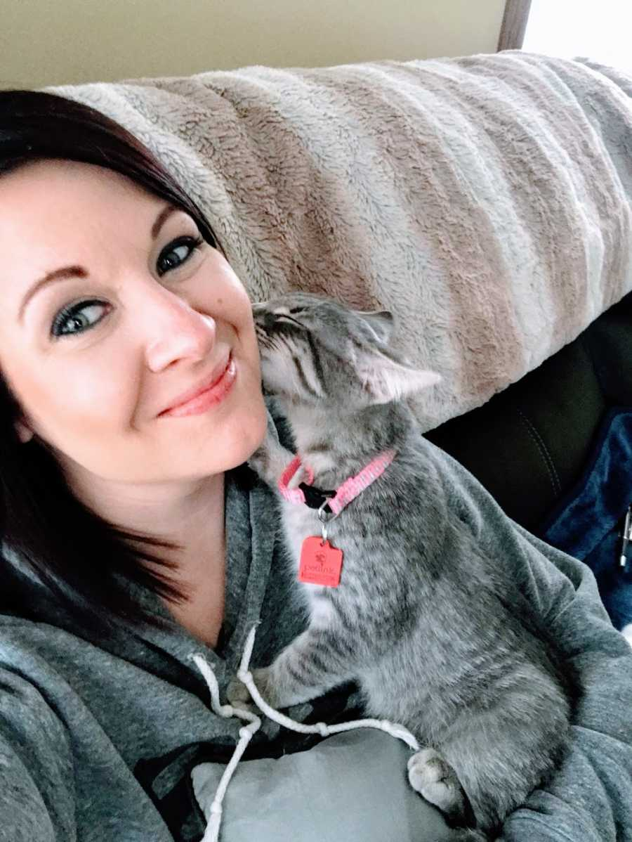 A woman sits on her couch with a kitten licking her face
