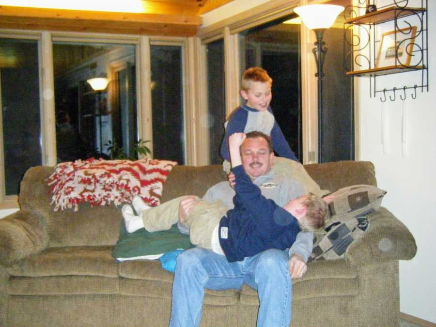 Father sitting on couch with one son on lap and the other standing behind him