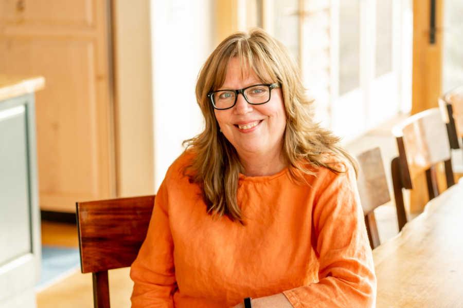 Woman wearing orange shirt smiling