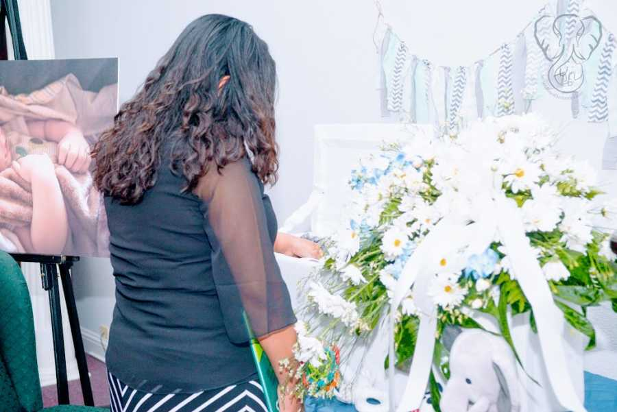 A single mother by choice grieves her stillborn son at his funeral