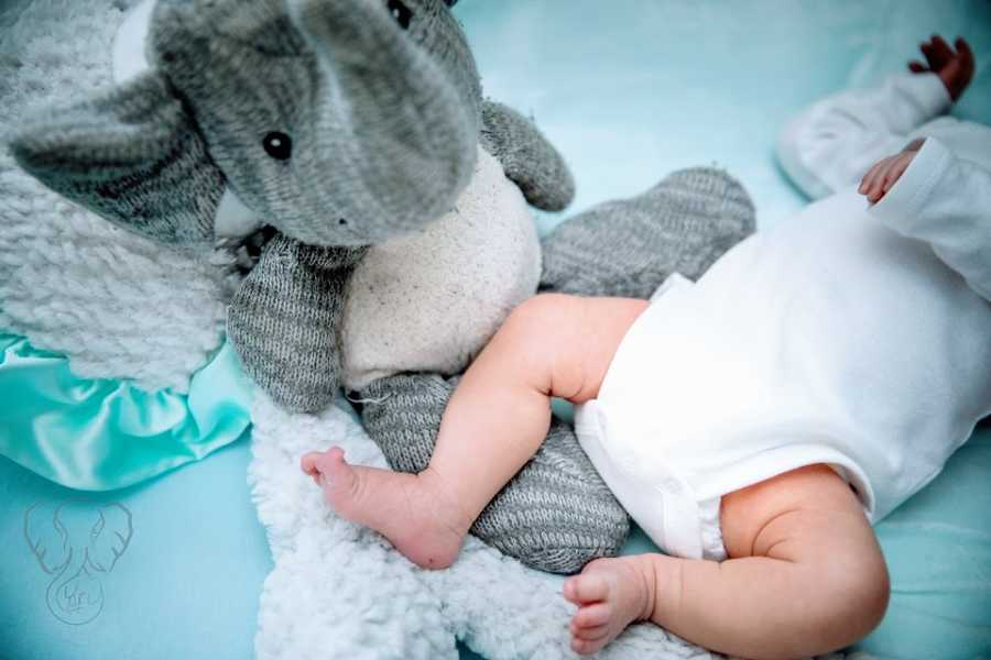 A baby girl's feet next to her deceased brother's toy elephant