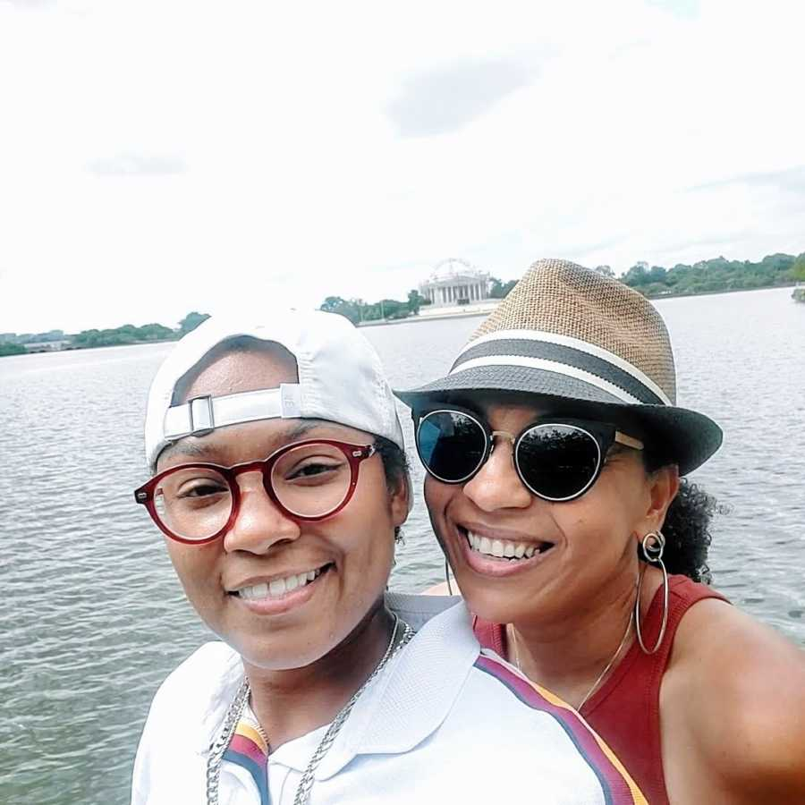 A lesbian woman and her wife by the water wearing hats