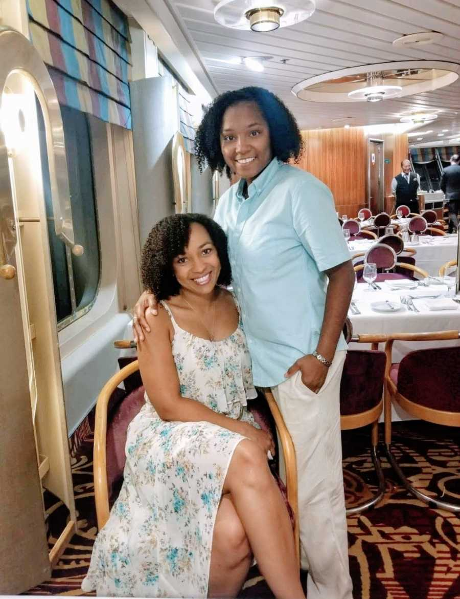 A Black woman sits in a chair while her wife stands with her arm around her